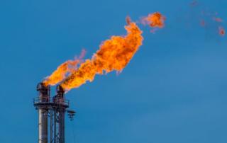 A gas flare spews fire toward the sky.