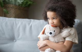 A little girl anxiously hugs a teddy bear as she sits on a couch.
