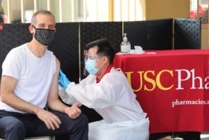 A trim, gray-haired man gets a flu shot.