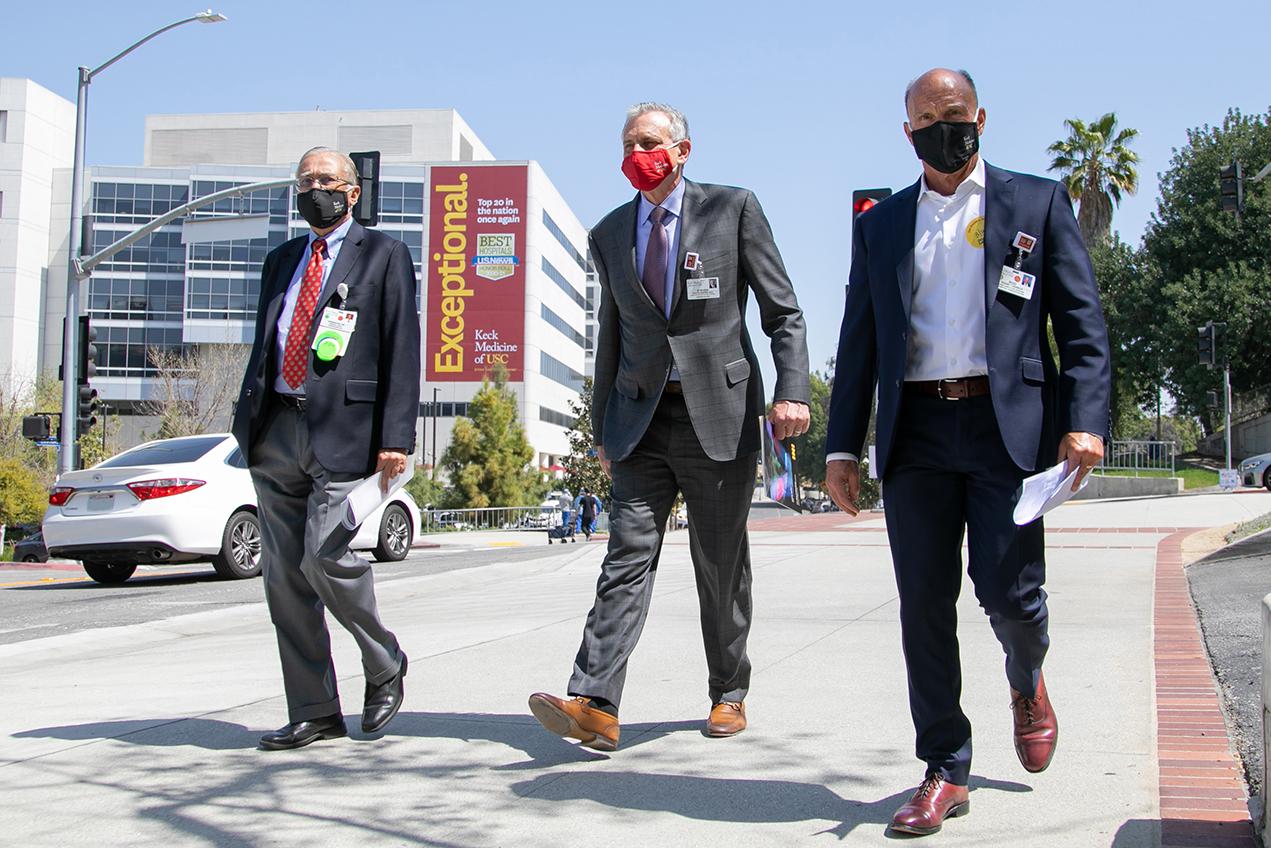 Three masked men wearing suits walk down a sidewalk