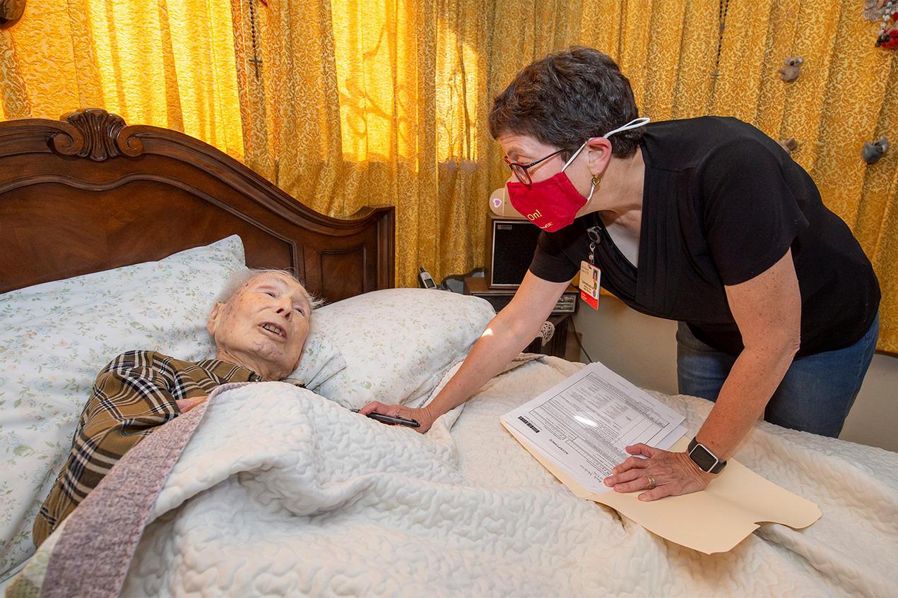 Laura Mosqueda talks with Manuel Grijalva, 98, before giving him his COVID-19 vaccination at his home.