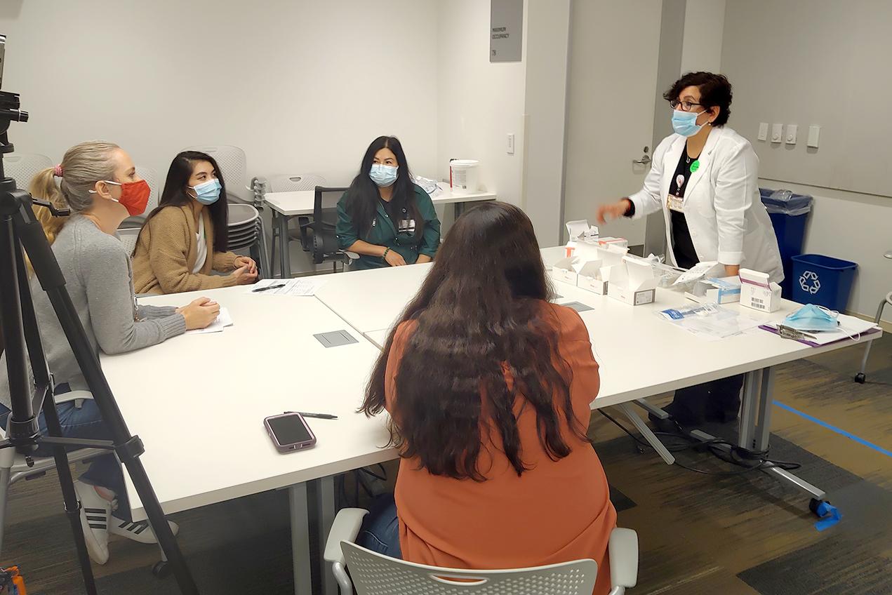 Nurse navigator Daphne Bautista demonstrates tracheostomy equipment during a training session.